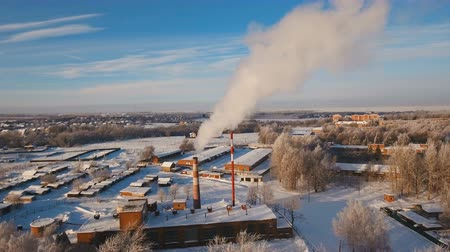 termal : Boiler room in the winter season, from the chimneys rise up clouds of steam. Pipes of a thermal power plant. Boiler house, pipe plant, boiler plant. Aerial footage, 4K video.