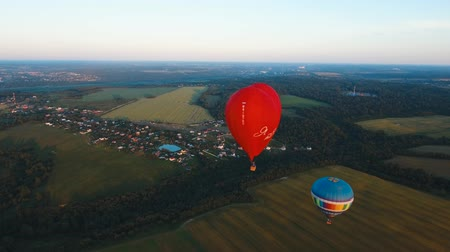 dirigível : Aerial view Hot air balloon shape of a heart in the sky over a field in the countryside, beautiful sky and sunset. Aerostat fly in the countryside.Aerial footage, 4K