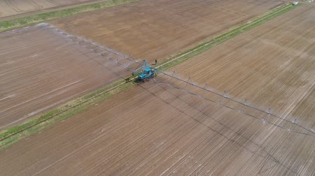 выращивание : Aerial view of Crop Irrigation using the center pivot sprinkler system. An irrigation pivot watering agricultural land. Irrigation system watering farm land.