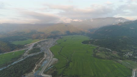terra : Aerial view of farmer fields, river, village in the background of mountains at sunset on the island of Luzon, Philippines. Mountain landscape with valley and village.