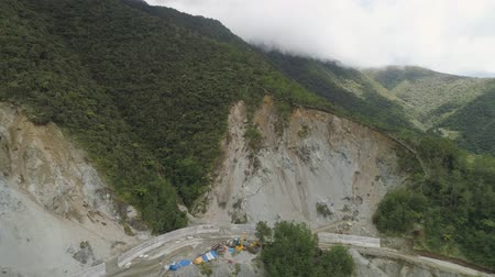 landslide : Construction of protective barriers against rock falls and landslides in the mountainous province. Aerial view of heavy machinery on the construction of a mountain road. Cement block road protection from landslides. Philippines, Luzon, North Batad. Stock Footage