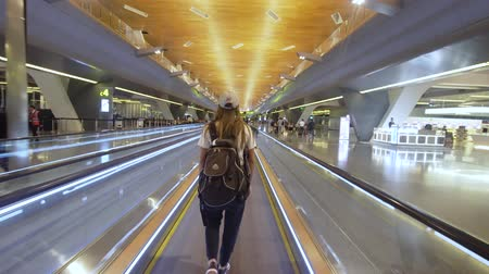 Girl with a backpack on a horizontal escalator at the airport. Tourist in a modern airport. Exterior of the new Hamad International Airport in Doha, Qatar. Inside the airport with modern infrastructure.