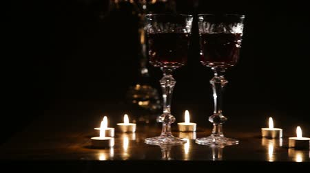 goblet : Two glasses of wine on black background and burning candles..Glasses of red wine over candlelight and darkness..Slider video footage.Romantic evening with wine. Stock Footage