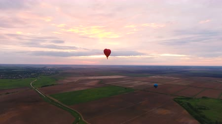 tej : Hot air balloons in the sky over a field in the countryside.Aerial view:Hot air balloons in the sky over a field in the countryside the beautiful sky and sunset. 4K video,ultra HD.