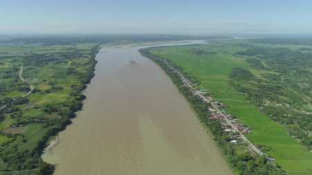 terra : River passing through farmlands and rice terraces. Philippines, Luzon. Aerial view of river, agricultural land against blue sky. Stock Footage