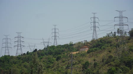 pilon : Power pylons and high voltage lines passing through mountain cordillera. Philippines, Luzon. High voltage metal post, tower. Electric Power Transmission Lines over trees.