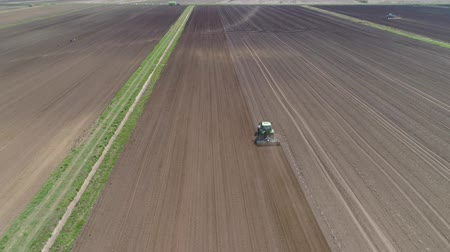 tırmık : Aerial view of Tractor with harrows prepares the agricultural land for planting the crop. Cultivation of farmland by disc harrows.