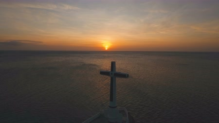 césar : Aerial view Sunken Cemetery cross at sunset in Camiguin Island, Philippines. Large crucafix marking the underwater sunken cemetary of the coast of camiguin island near mindanao in the Philippines. Catholic cross in the water on the background of sky and c