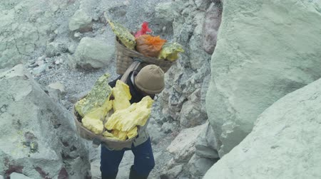 sulfur : Worker carries a basket with pieces of sulfur on his shoulder. Sulfur miners carries sulfur from inside the crater of Kawah Ijen volcano in East Java, Indonesia. Stock Footage