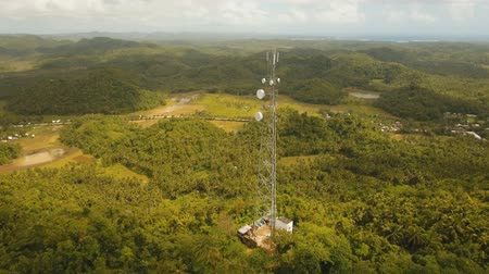 transmitter tower : aerial footage telecommunication tower located located in mountainous province. cellphone tower in rainforest white telecom radio tower