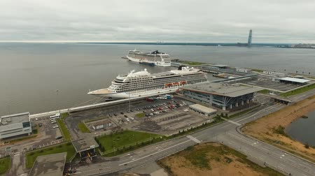 porto : Large ocean cruise ship moored in seaport. Aerial view Sea port in St. Petersburg with a cruise ship. drone footage, 4k. Stock Footage