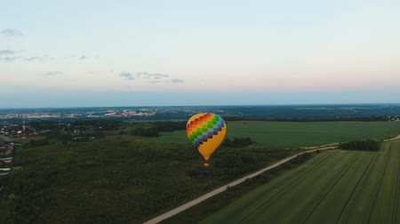 vzducholoď : Aerial view Hot air balloon in the sky over a field in the countryside in the beautiful sky and sunset. Aerostat fly in the countryside. Aerial footage, 4K