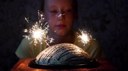 csillagszóró : girl looking at cake with sparkles and Bengal light in dark room