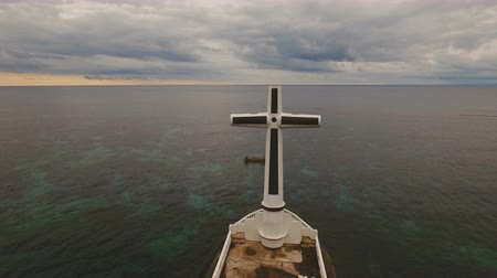 mindanao : Aerial view Sunken Cemetery cross in Camiguin Island, Philippines. Large crucafix marking the underwater sunken cemetary of the coast of camiguin island near mindanao in the Philippines. Catholic cross in the water on the background of sky and clouds.. Th Stock Footage