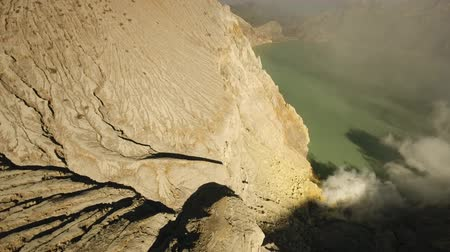 flying video : Extraction of sulfur in the crater of a volcano. Sulfur, sulfur gas, smoke. Kawah Ijen, crater with acidic crater lake the famous tourist attraction, where sulfur is mined. Aerial view of Ijen volcano complex is a group of stratovolcanoes in the Banyuwang Stock Footage