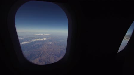 rozsah : Mountain range from the airplane window. Airplane wing. Aerial view on mountains through window of an aircraft. Travel concept.