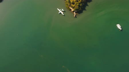 hydroplane : aerial white Seaplane in the sea bay. hydroplane on the water surface near the shore Travel concept, Aerial footage. Stock Footage