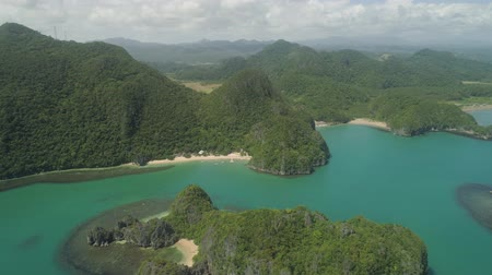 luzon : Aerial view of islands with sand beach and turquoise water in blue lagoon among coral reefs, Caramoan Islands, Philippines. Mountains covered with tropical forest.
