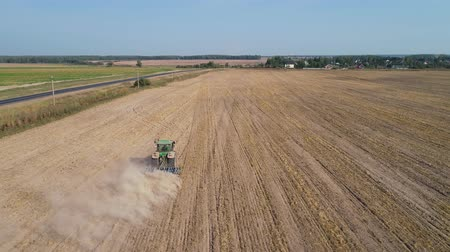 tırmık : aerial footage tractor with disk plow prepares field after harvesting wheat. Tractor with harrows prepares the agricultural land for planting the crop. Cultivation of farmland by disc harrows. Stok Video