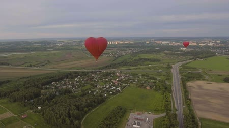 tej : Red balloon in the shape of a heart.Aerial view:Hot air balloon in the sky over a field in the countryside,the beautiful sky and sunset.
