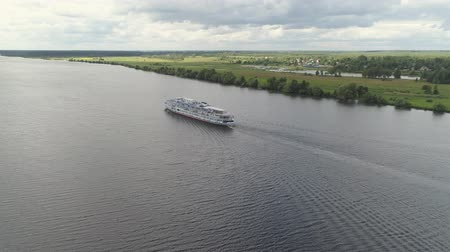 személyszállító hajó : Aerial view large white cruise ship on river Volga in countryside. Cruise ship on the river through the green trees.