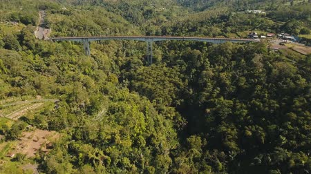 kaňon : Bridge with car road over mountain canyon, mountains, rainforest. Aerial view of bridge in a mountain gorge above a green jungle among the mountains. Bali, Indonesia. 4K video. Aerial footage. Dostupné videozáznamy