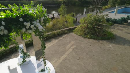 церемония : aerial footage wedding ceremony with arch decorated with cloth and flowers outdoor. wedding set up in the park on a sunny day, arch and chairs for guests
