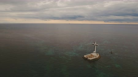 párat se : Aerial view Sunken Cemetery cross in Camiguin Island, Philippines. Large crucafix marking the underwater sunken cemetary of the coast of camiguin island near mindanao in the Philippines. Catholic cross in the water on the background of sky and clouds.. Th Dostupné videozáznamy