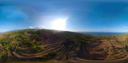 flying video : vr360 landscape mountains with farmlands, village, fields with crops, trees against backdrop of the sea coast. Aerial view of Mountains are covered with forest. Bali, Indonesia.