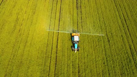 трактор : Aerial view tractor spraying the chemicals on the large green field. Spraying the herbicides on the farm land. Treatment of crops against weeds. 4K, aerial footage.