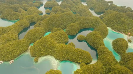 flying video : aerial footage lot islands in lagoon with turquoise water Bucas Grande Island Sohoton Cove. islands covered with green tropical forest surrounded by beautiful bays and lagoons tropical seascape blue sea, azure lagoon. Flying over the azure surface ocean.