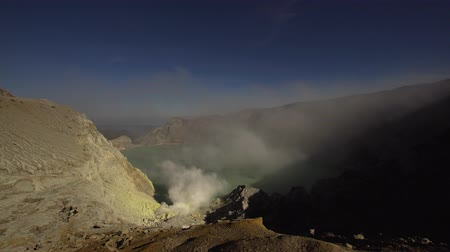 кратер : Crater with acidic crater lake Kawah Ijen the famous tourist attraction, where sulfur is mined. Extraction of sulfur in the crater of a volcano. Sulfur gas, smoke.