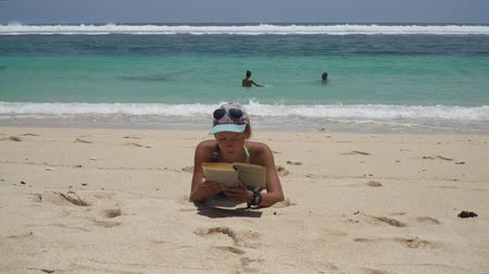 Girl lies on a sandy beach and reads a book. Young girl on vacation reading a book on the seashore with azure water. Travel concept.Bali, Indonesia.