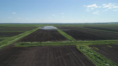 spil : Aerial view crop Irrigation using center pivot sprinkler system. An irrigation pivot watering agricultural land. Irrigation system watering farm land.