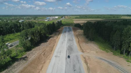 掘削機 : Construction of toll roads in rural areas. Aerial view construction of a new highway next to the old highway.