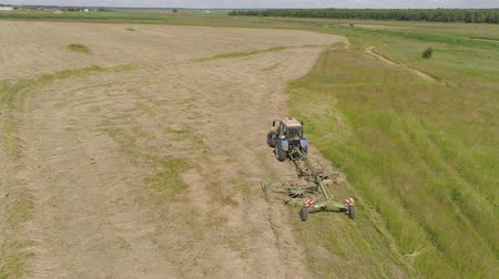 így : Aerial, view agricultural machinery with wheeled rake makes ranks beveled hay.Tractor which is lining up dried grass getting it ready for pickup so it can be used as animal fodder summer day. Stock mozgókép