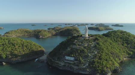 pilgrimage : Small islands in Hundred Islands National Park with statue of Jesus Christ, Pilgrimage, Pangasinan. Aerial view of group of small islands with beaches and lagoons, famous tourist attraction, Alaminos, Philippines. Stock Footage