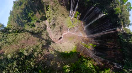 küresel : little planet view waterfall in green rainforest. Coban sewu aerial view tropical waterfall in mountain jungle, Indonesia. Travel concept. Aerial footage. Stok Video