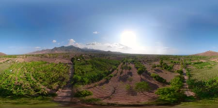 flying video : vr360 landscape mountains with farmlands, village, fields with crops, trees, sea coast. Aerial view village by sea Indonesia.