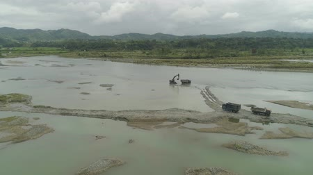 dredging : Aerial view of Excavator and heavy equipment, dredging and deepening the channel of the mountain river. Heavy dredging machine on a river bank. Excavator dredge a river. Philippines, Luzon. Stock Footage