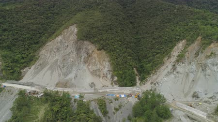 трактор : Construction of protective barriers against rock falls and landslides in the mountainous province. Aerial view of heavy machinery on the construction of a mountain road. Cement block road protection from landslides. Philippines, Luzon, North Batad. Стоковые видеозаписи