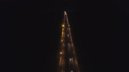 中断 : aerial view lighted bridge at night with highways and cars. suspension bridge over madura strait with highway and car, surabaya. aerial view bridge Suramadu connecting islands Java and Madura. High co 動画素材