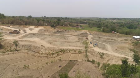 buldozer : excavator at construction site cuts hill and loads truck with earth. aerial view Heavy machinery prepares the countryside for construction. Excavators are been used in large and small scale constructions Indonesia Stok Video
