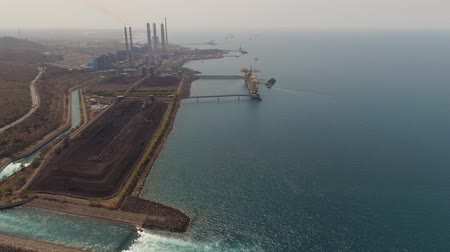 絶縁 : power station with spillway by sea with smoking pipes, paiton java, indonesia. aerial view power plant in asia.