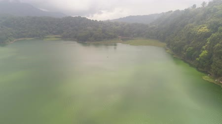 jezioro : lake Buyan shores covered with tropical vegetation on cloudy day. mountain with slopes covered tropical vegetation. Bali Landscape, lake among mountains, sky, clouds.