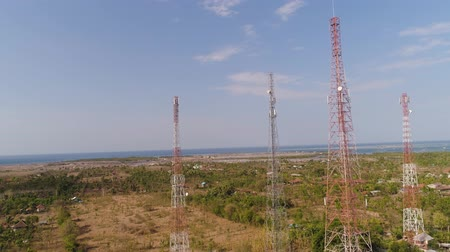 továbbít : aerial view cell phone towers line in bali, indonesia. Telecommunication tower, communication antenna on coast sea Stock mozgókép