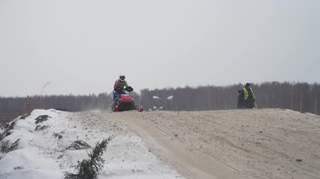 Russia, Championship on snowmobiles January 27, 2018: Winter racing on snowmobiles. Snowmobile on the route in a jump. Action from snowmobile races.