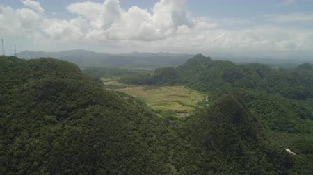 épico : Aerial view omountains covered rain forest, trees with clouds and sky. Luzon, Philippines. Slopes of mountains with evergreen vegetation. Mountainous tropical landscape. Cordillera region. Stock Footage
