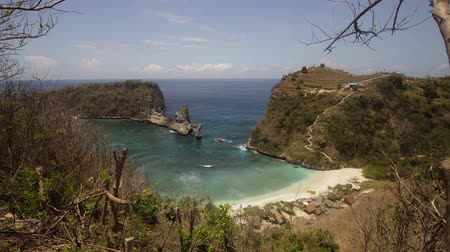 costa azzurra : Beach with with azure water, rocky mountains and clear water at sunny day. Clear blue ocean waves rolling to the beach. Nusa Penida, Bali, Indonesia. Travel concept.