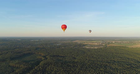 globos de aire caliente : Aerial view Hot air balloons in sky over forest in countryside, beautiful sky and sunset. Aerostat fly over countryside. Aerial footage 4K